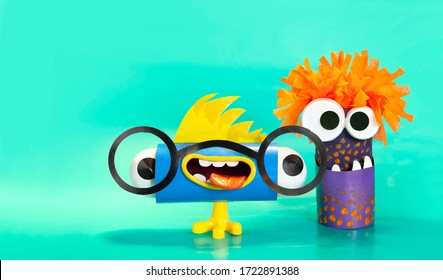 Close-up of monsters, aliens from a toilet roll and colored cardboard on a blue background. School and kindergarten. Handmade Creative Idea