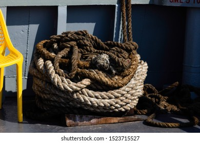 Close-up of a mooring rope with a knotted end tied around a cotter pin on a wooden pier. Nautical rope mooring.