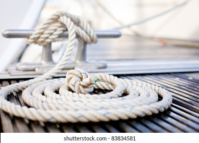 Close-up of a mooring rope with a knotted end tied around a cleat on a wooden pier/ Nautical mooring rope