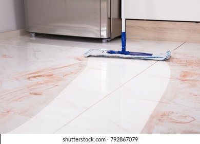 Close-up Of Mop In Kitchen Cleaning Dirty Floor At Home