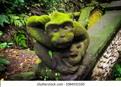 Closeup of a moss covered statue of a cute monkey in the Monkey Forest of Ubud, Bali, Indonesia