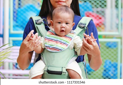4f646e2b5d8 Close-up mother carrying her infant by ergonomic baby carrier.
