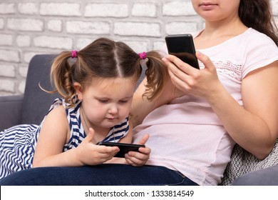 Close-up Of Mother And Daughter Sitting On Sofa And Using Mobilephone At Home