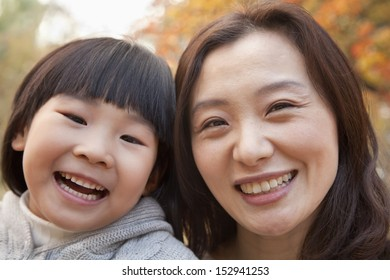 Close-up of Mother and Daughter smiling in the park, autumn, Portrait