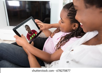 Close-up Of Mother And Daughter Video Conferencing On Tablet At Home