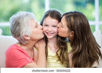 Close-up of mother and grandmother kissing happy girl on sofa at home