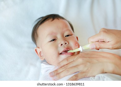 Close-up mother hand clean baby teeth and tongue with soft rubber brush.