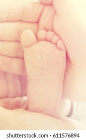 Closeup of mother hands holding cute tiny baby feet, showing baby foot. Selective focus. Toned.