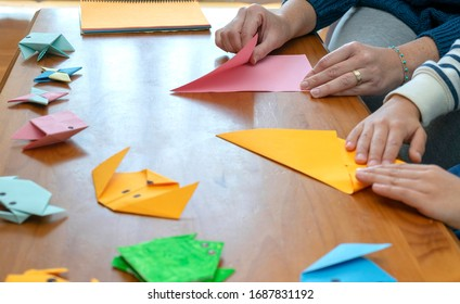 Close-up of a mother with her son while they are at home doing origami crafts