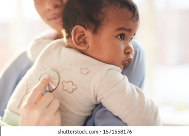 Close-up of mother holding baby on her hands with doctor listening to his heartbeat with stethoscope