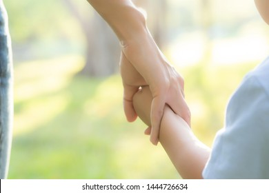 Closeup mother or parent and son holding hand with love together in summer outside in the park, mom take care kid holding palm with affection, child have a trust for mother, family concept.