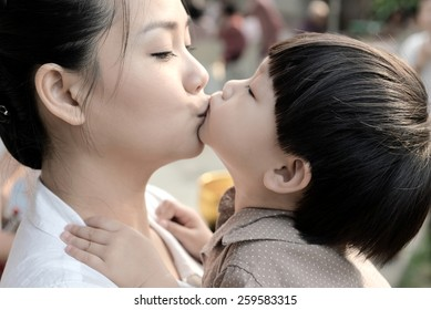 Closeup mother and son kissing together