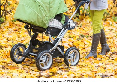 Close-up of mother strolling a pushchair with a sleeping baby in yellow autumn park