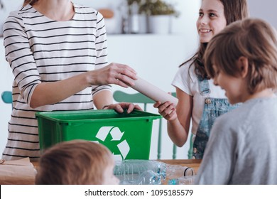 Close-up of mother teaching kids how to segregate waste at home