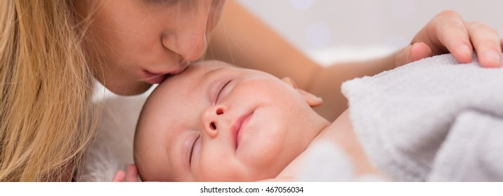 Close-up of a mother tenderly kissing her sleeping newborn's head