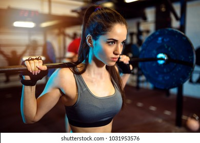 Close-up of motivated focused attractive young fitness woman doing squads exercise in the gym.