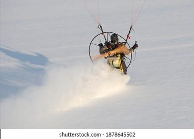 Gros plan sur un parapente à moteur vu du ciel volant en hiver dans un paysage blanc et laissant une piste dans la neige