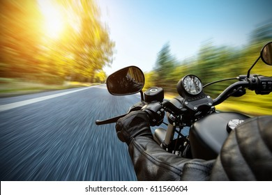 Close-up of motorbiker riding on empty road in forest with sunrise light, concept of speed and travel in nature