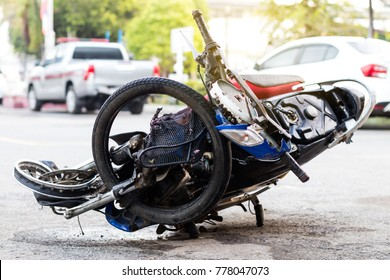 Close-up of a motorcycle, crushed by a severe accident, was placed on a paved road near the fence.