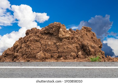 Close-up of a mound of dirt near the side of a paved road with sky clouds as a backdrop in rural Thailand.