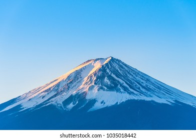Close-up of Mount Fuji view with Lake Kawaguchi and clear blue sky background in Kawaguchiko, Japan Peak of Fuji mountain cover with snow and shading with golden sunlight in the morning.