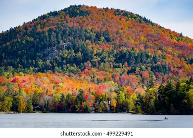 A closeup of a mountain with colorful autumn foliage across Mirror Lake in Lake Placid on a sunny fall day