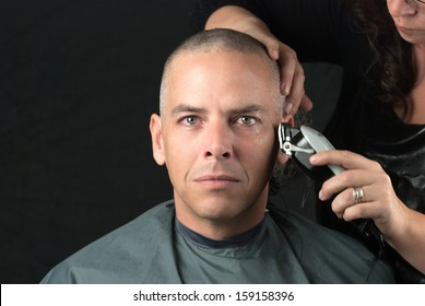 Close-up of a mourning man getting his head shaved. Looking to camera,
