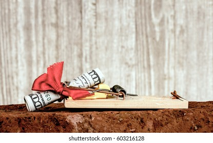 Closeup of a mouse trap set atop of a red brick with a hundred dollar bill rolled up in side a red bow set on the mouse trap which has been triggered and is grasping the bill.