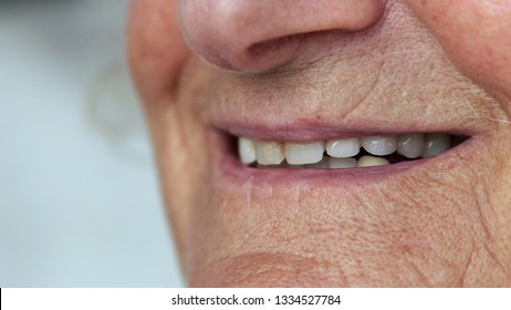 Closeup mouth of elderly woman talking and smiling with perfect teeth