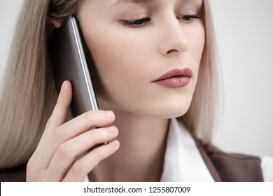 Close-up of the mouth and lips of a woman talking on a smartphone on a white background. White beautiful teeth. Customer support.