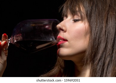 Closeup of the mouth and sexy red lips of a young woman drinking red wine from a wineglass against a dark background