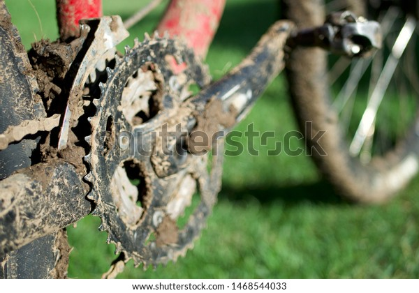 Close-up of muddy crankset on red mountain bike after a ride.