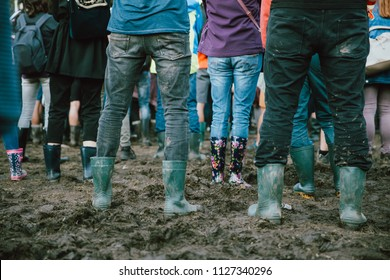 Closeup of muddy wellingtons. People attending on a rainy day at a music festival.