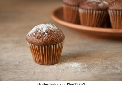 close-up of a muffin on the background of a plate with muffins, selective focus.