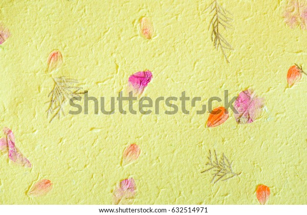 Closeup of mulberry paper embedded with green grass, leaves and petal. Mulberry paper are made from the woody bast fiber that used from inner bark of the paper mulberry tree (Broussonetia Papyrifera).