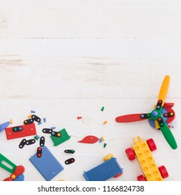 Closeup of multi-color plastic toys and bricks on white wooden background. Early learning and development.