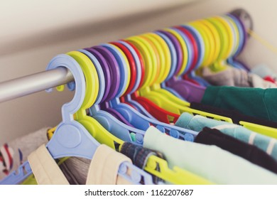 Closeup of multicolored hangers in a closet, Toddler clothes hanging on plastic colorful hangers. No retouch, natural lighting, filter applied.
