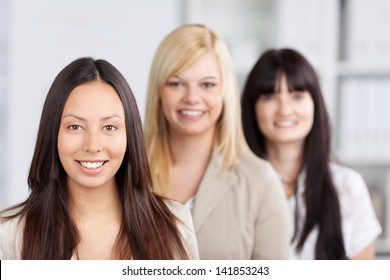 Closeup of multiethnic businesswomen smiling together in office