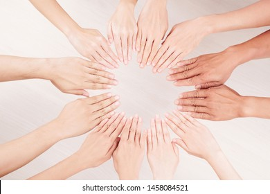 Close-up of multiethnic group of people putting their hands on the table in the form of circle