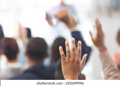Close-up of multi-ethnic hands being raised in a business seminar in office building