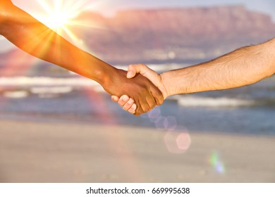Closeup of multiethnic handshake at Table Mountain beach