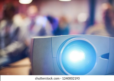 Close-up multimedia projector with blurred people background.