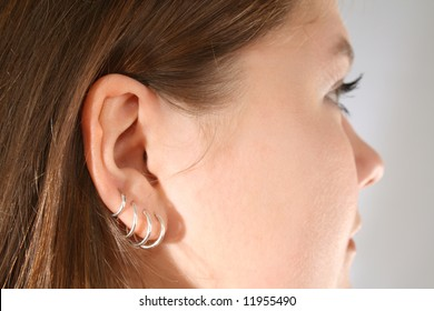 Close-up of multiple ear piercings on young girl.