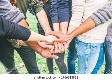 Closeup of multiracial people putting hands on stack  - Group of friends with mixed races getting ready for teamwork effort - Friendship and lifestyle concepts