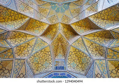 The close-up of the muqarnas (honeycomb) arch of the West portal of Jameh mosque, the brick cells are covered with intricate mosaic patterns, Isfahan, Iran.