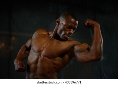 Close-up muscles of african american handsome body builder posing with naked torso on the black studio background
