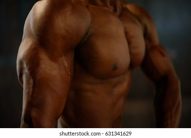 Close-up muscles of african american man model posing with naked torso on the black studio background