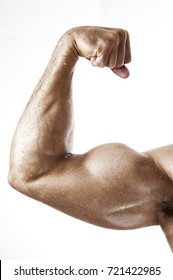 Closeup of muscular fitness model showing biceps muscles. Young man posing over white background.