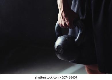 Close-up of a muscular hand holding a kettlebell