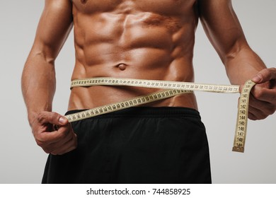 Close-up muscular man measuring stomach and abs with tape in studio.